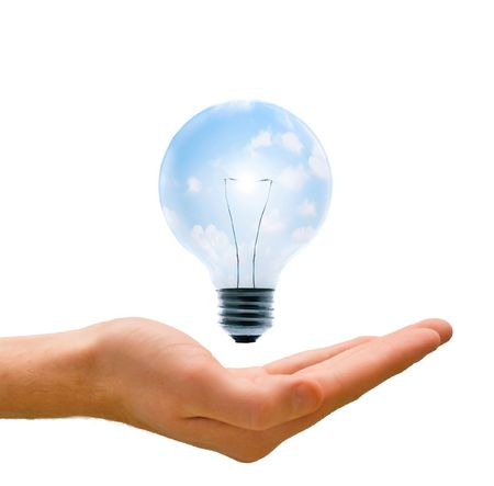 Clean energy, a light bulb with a bright sky held up by a hand. Stock Photo