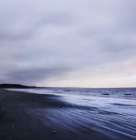 Dark sky over a pacific beach. Stock Photo