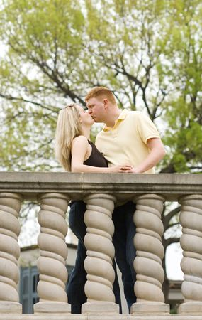 Young engaged couple kissing outdoors Stock Photo