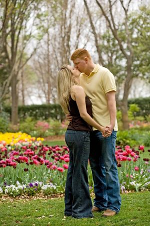 Young engaged couple kissing outdoors Stock Photo - 5412828