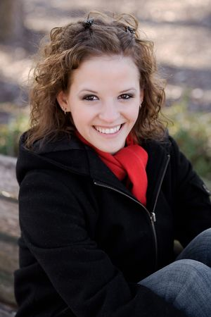 Closeup portrait of a beautiful young woman smiling with winter clothing.