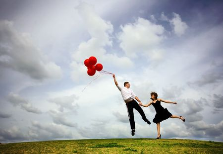 Cute Couple Flying met Red Balloons  Stockfoto