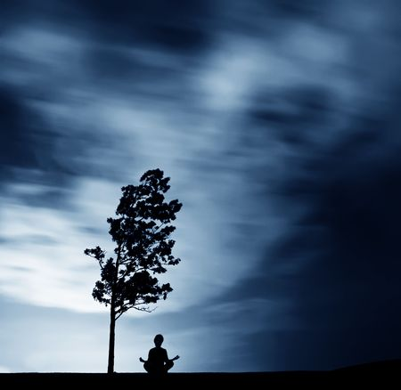 Silhouette Meditating Outdoors next to tree  Stock Photo