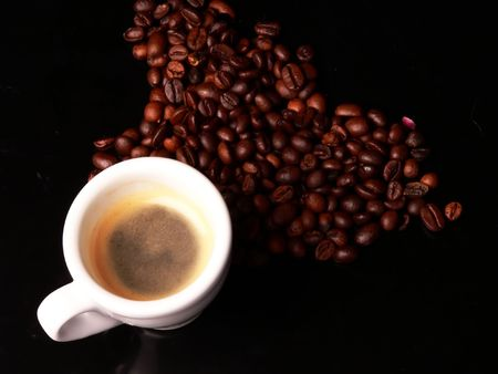 A cup of coffe with coffes bean around