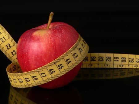 centimetres: An apple with a measuring tape around as a concept of good food good healt