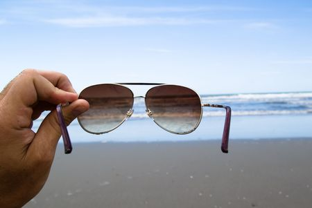 handhold: Handhold Sunglasses in front of a beach. vacation concept. Stock Photo