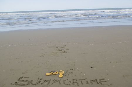 blu sky: Yellow flippers and Summertime written on the sand as a meaning of summer and vacation