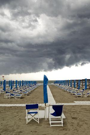 menacing: Menacing clouds over a beach with umbrella and seats, Italy Stock Photo