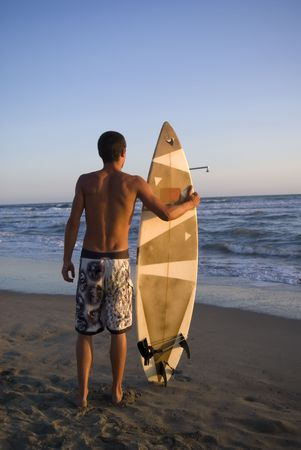 Surfer ready to enter in the water at sunset