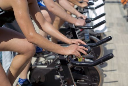 A group of people doing exercise with spinning bycicle in the walkway of Viareggio, Italy. Focus on the hand of the first man.