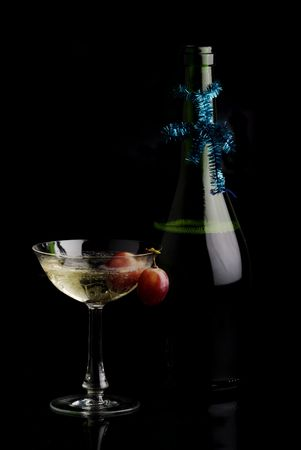 campagne: An adorned bottleneck, a glass of campagne wih red grapes. Concept for new years and christmas party