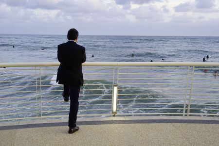 admiring: Businessman admiring young surfer at the seaside. Good concept for working stress, holiday concep.