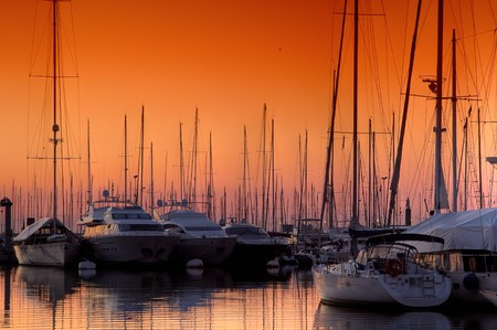 Extra Large Luxury yachts rest in the port at sunset Stock Photo