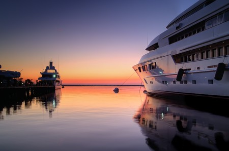 richness: Extra Large Luxury yachts rest in the port at sunset Stock Photo