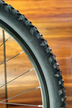 close up of a mountain bike wheel against a wooden panel photo