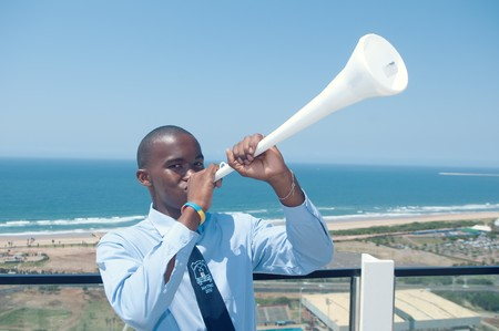 stadium  durban: DURBAN - MAY 04: Vuvuzuela is the trumpet of south african soccer fans.  A southafrican student singing it at the durban new stadium, may 04 2010 in Durban, SouthAfrica Editorial