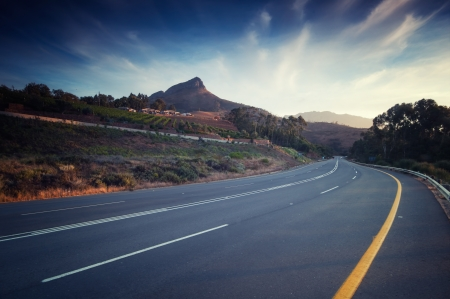 Road sneaks through vineyar at sunset in stellenbosch. Part of the wine route that represents more than 200 wine and grape producers within the boundaries of the Stellenbosch Wine of Origin classification. The Wine Route is divided into five sub-routes. photo