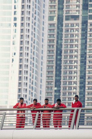 underpaid: NOV 26 -DUBAI, UAE:  Migrant workers on construction site of high-rise apartment skyscraper tower  on 26th november  2013 in Dubai,UAE.Dubai has approximately 250,000 laborers, mostly South Asian, working on real estate, often underpaid and in poor condit