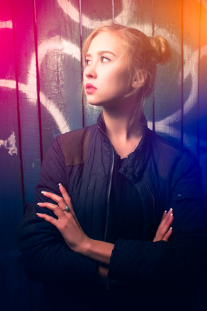 adds: Young girl poses with an arrogant expression against a grundge  background, color light flare adds tone to the composition