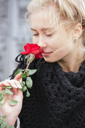 Beautiful girl smelling the scent of a rose at a market