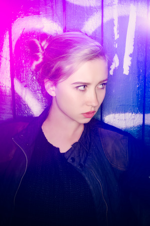 grundge: Young girl poses with an arrogant expression against a grundge  background, color light flare adds tone to the composition