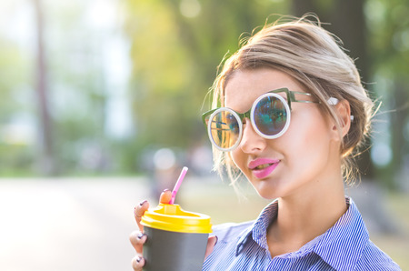 Beautiful girl drink coffe on the go, baclighting illumination
