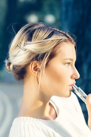 18's: Teenage girl using electronic cigarette