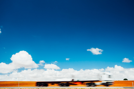 Motion blurred image of a transport truck on a Highway against a cloudy sky