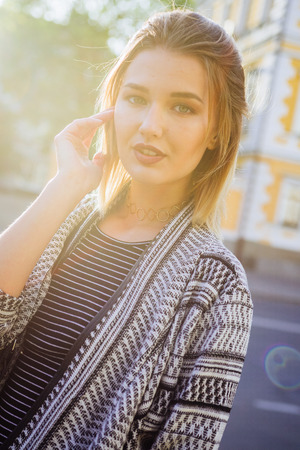 ropa casual: Beautiful blonde girl posing for the camera in an urban contest with city building in the background,strong backlighting.