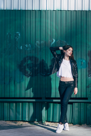 grundge: Young beautiful brunette walk in a city against a grundge background and a strong backlight