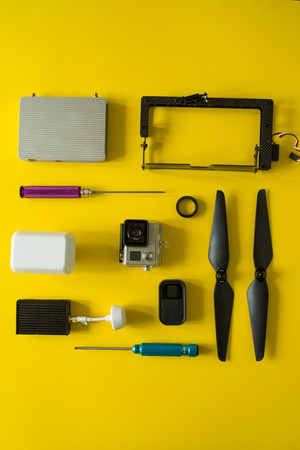 Top view of drone components, included propellers, video link, digital transmitter and screwdriver  on a yellow background