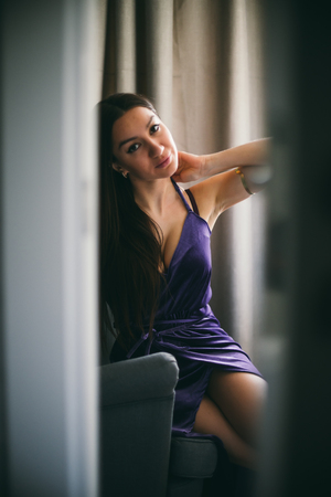 Sexy beautiful girl posing in a  room with violet dress, photographed in a paparazzi spied style with foreground unfocused Stock Photo