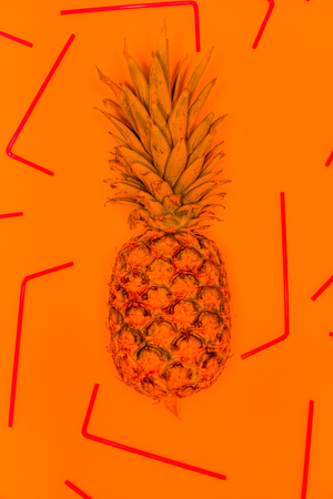 flashy: Concept of summer with a ananas shot between p straws against a orange  background, orange tint added. Stock Photo