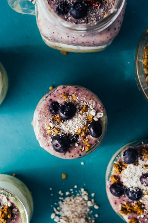 Top view of a delicious breakfast yogurt parfait made with fresh yogurt, strawbery smothie and ananas smoothie with granola layer and blueberry as decoration on a rusty blue tint green wooden table