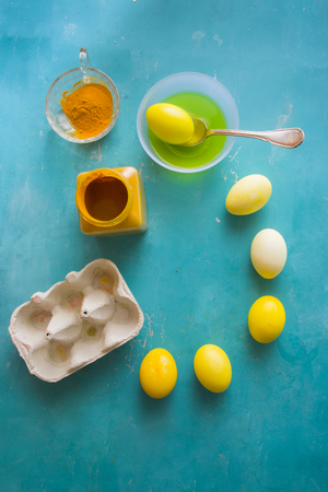 Dyeing eggs for Easter holidays,using natural ingredients curcuma to create a yellow tonality over a blue concrete background Stock Photo