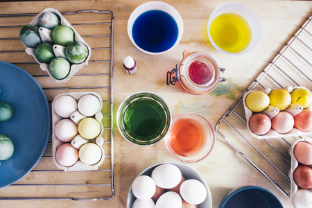Dyeing eggs for Easter holidays, coloring with different color and tonality using food colorant over a gray concrete background