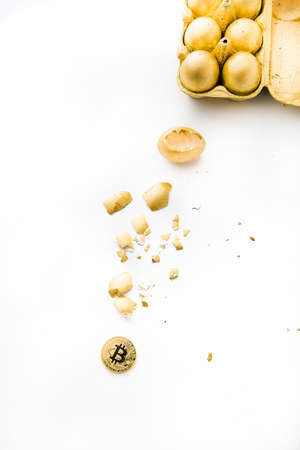 One old aesopus story  tells about the chick who makes the golden egg, in this case she makes bitcoin, conceptual composition for bitcoin and new economy, with golden eggs cracked with bitcoin outside Stock Photo