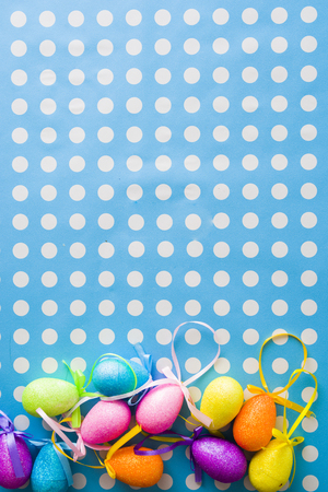 Colored decoration eggs for Easter holidays over a blue and pois white background