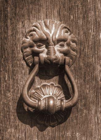 a lion head knocker on a wood door photo