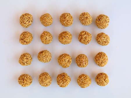 White sesame seed balls made with heated jiggery, tasty and nutritious candy , against white background