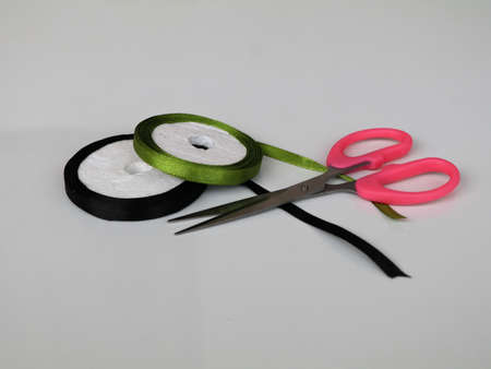 Satin ribbon rolls with scissors  against white background, isolated