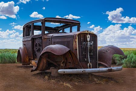 A low angle view of an old abandoned, antique, vintage automobile circa 1930 on the side of the road at the Petrified Forest National Park marks the path of old Route 66