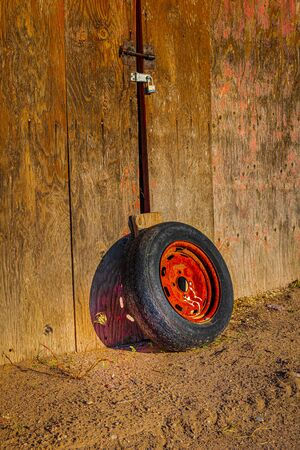 A well-used red-rimmed tire sits agaiinst a shed door as the sun casts an interesting shadow on the wood