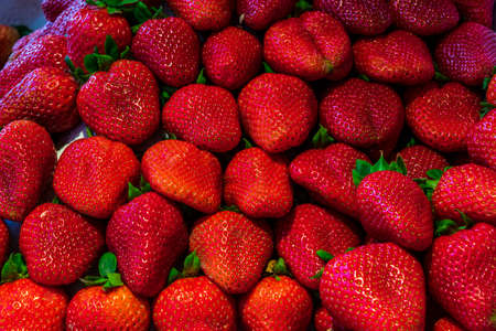 Summer bounty of beautiful red, ripe, large strawberries at a local market.