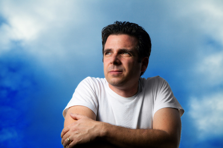 trustworthy: A handsome man looks off in the distance against a blue, slightly cloudy sky.  He is wearing a white t-shirt and is lit from the side.  His wedding ring is prominent.  He looks serious, intense, determined, hopeful.