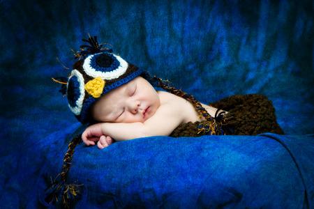 catnap: A sleeping newborn boy takes a catnap while an crocheted owl hat.