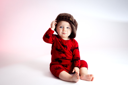cocky: A sly looking baby boy sits with a side tipped hat.  He is looking off camera with a confident and slightly cocky look on his face. He is wearing red pajamas with moose print and a knit visor tam style hat. Stock Photo