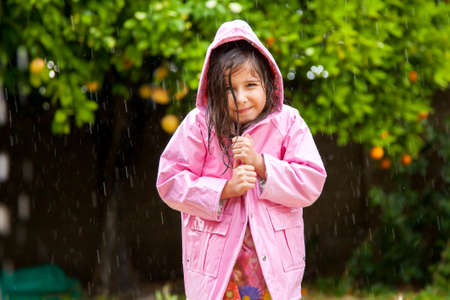 mischevious: A sweet little girl pulls her pink raincoat closed as she stands happily in a Spring shower. Stock Photo