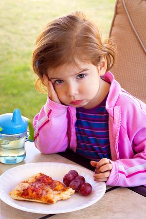 ふくれっ面と部分的に食べて食品のプレートの前に明白な幼児の女の子が座っています。 写真素材