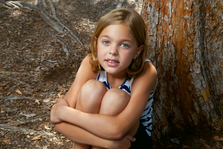 insecure: A young girl sits by a tree, hugging her legs, as she looks up at the camera.  She has a slightly confused look, almost a smile.